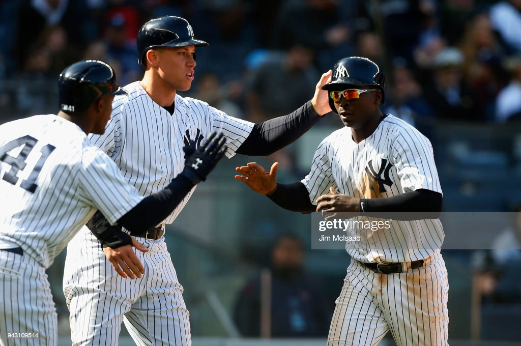 Didi Gregorius #18 and Aaron Judge #99 of the New York Yankees celebrate with teammate Miguel Andujar #41 after both scored in the seventh inning against the Baltimore Orioles at Yankee Stadium on April 7, 2018 in the Bronx borough of New York City.