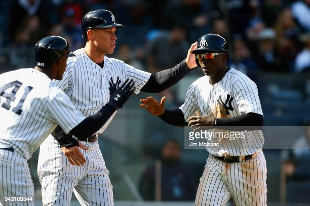 Didi Gregorius and Aaron Judge of the New York Yankees celebrate with teammate Miguel Andujar after both scored in the seventh inning against the...