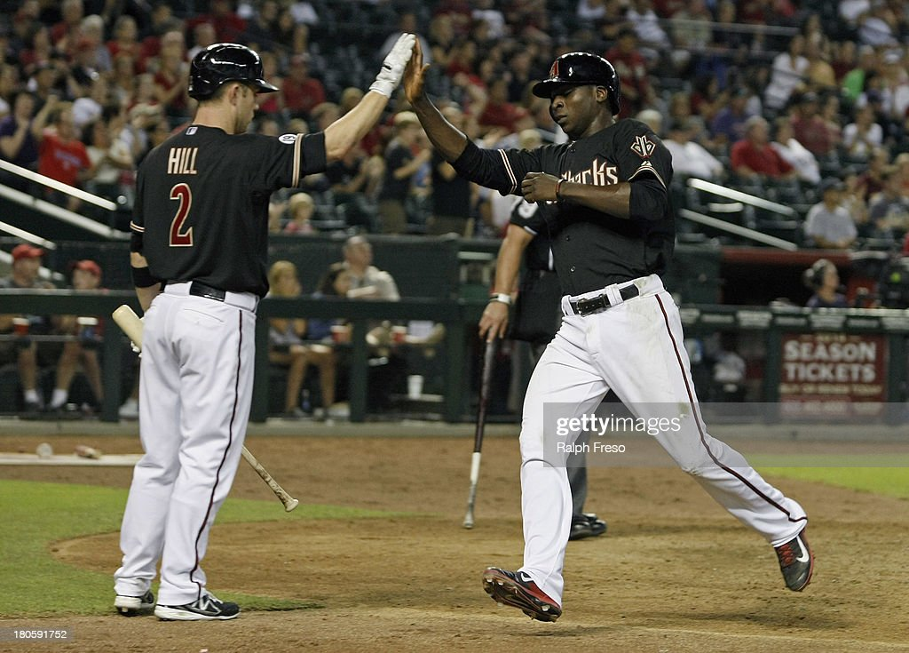 Didi Gregorius #1 of the Arizona Diamondbacks is congratulated by teammate Aaron Hill #2 after scoring against the Colorado Rockies during the eighth inning of a MLB game at Chase Field on September 14, 2013 in Phoenix, Arizona.