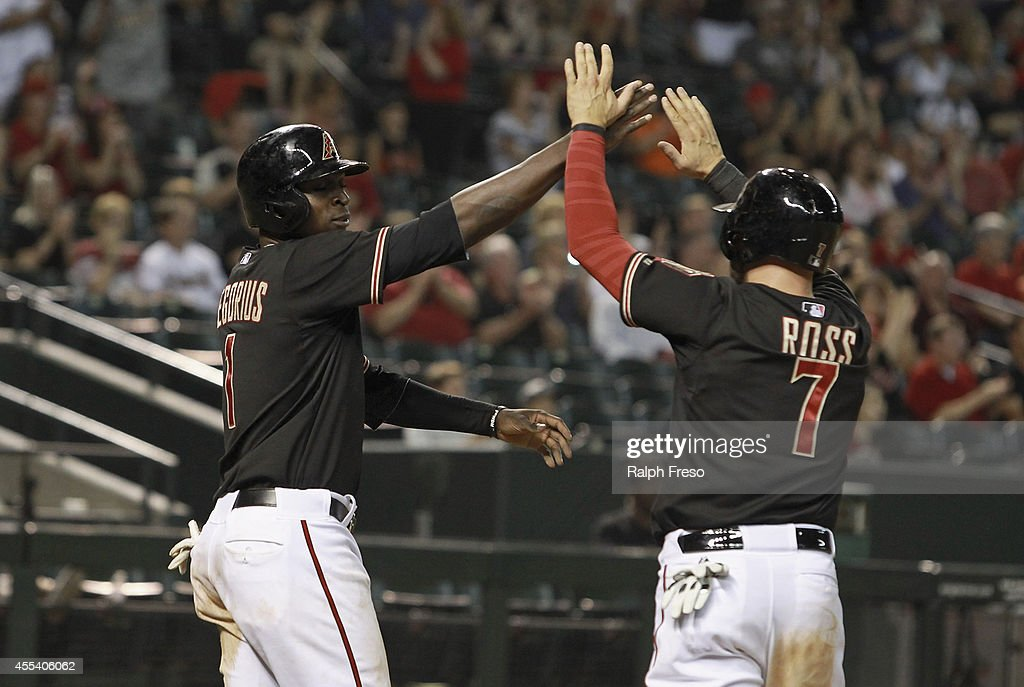 Didi Gregorius #1 of the Arizona Diamondbacks is congratulated by teammate Cody Ross #7 of the Diamondbacks after scoring against the San Diego Padres during the seventh inning of a MLB game at Chase Field on September 13, 2014 in Phoenix, Arizona. The Diamondbacks defeated the Padres 10-4.
