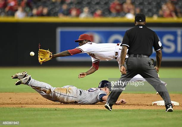 Didi Gregorius of the Arizona Diamondbacks makes a diving catch over the top of a sliding Matt Dominguez of the Houston Astros during the eighth...
