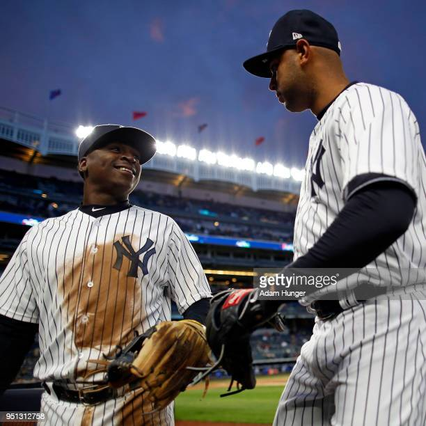 Didi Gregorius of the New York Yankees and Aaron Hicks of the New York Yankees in action against the Toronto Blue Jays during the third inning at...