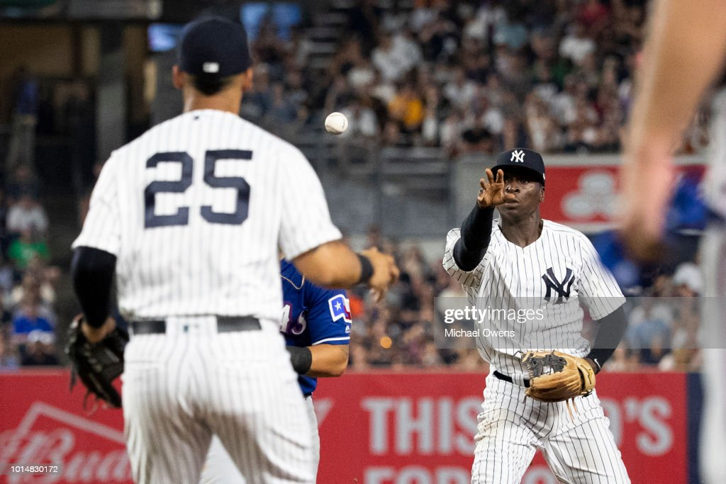 Didi Gregorius #18 of the New York Yankees attempts to flick the ball to Gleyber Torres #25 of the New York Yankees during a rundown in the sixth inning against the Texas Rangers during their game at Yankee Stadium on August 10, 2018 in New York City.