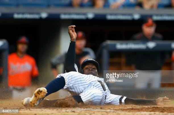 Didi Gregorius of the New York Yankees avoids the ball as he slides home for a run in the fifth inning against the Baltimore Orioles at Yankee...