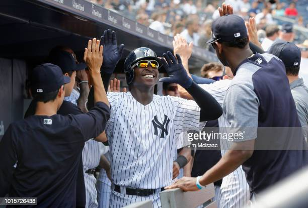 Didi Gregorius of the New York Yankees celebrates his fifth inning two run home run against the Texas Rangers with his teammates in the dugout at...