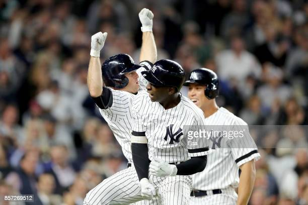 Didi Gregorius of the New York Yankees celebrates with Brett Gardner and Aaron Judge after hitting a three run home run against Ervin Santana of the...