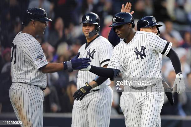 Didi Gregorius of the New York Yankees celebrates with Edwin Encarnacion after his grand slam home run off Tyler Duffey of the Minnesota Twins in the...