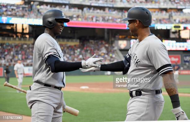 Didi Gregorius of the New York Yankees congratulates teammate Aaron Hicks on a solo home run against the Minnesota Twins during the third inning of...