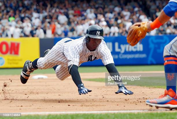 Didi Gregorius of the New York Yankees dives into third base safely with a triple in the fourth inning of an interleague MLB baseball game against...