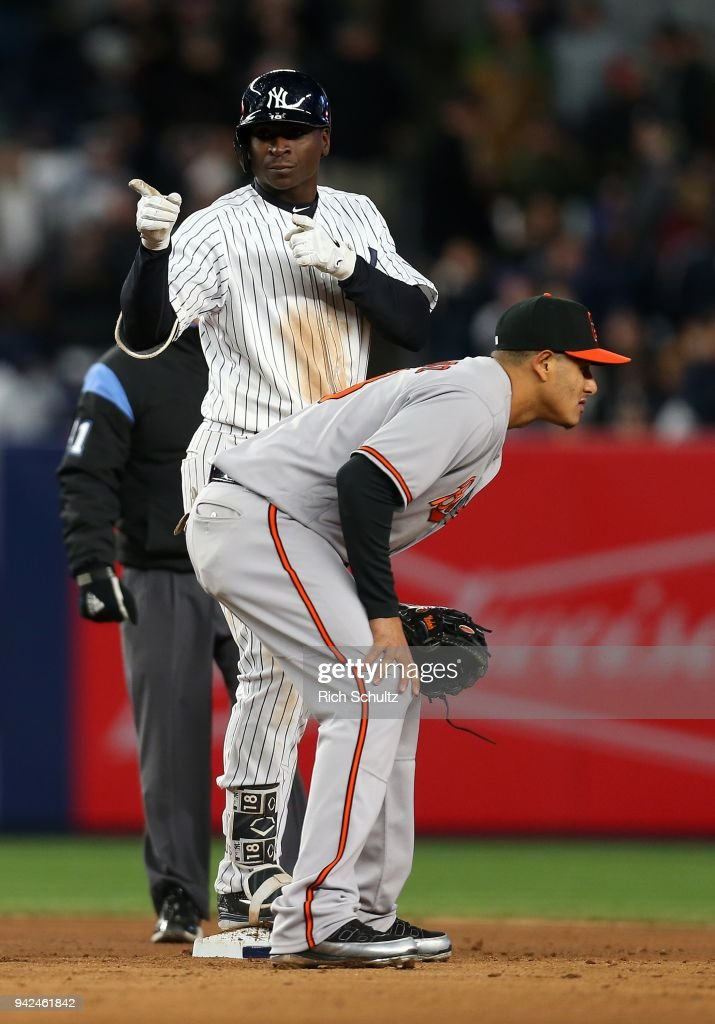 Didi Gregorius #18 of the New York Yankees gestures behind shortstop Manny Machado #13 of the Baltimore Orioles after hitting a double during the seventh inning of a game at Yankee Stadium on April 5, 2018 in the Bronx borough of New York City.
