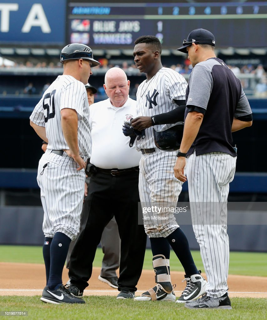 Didi Gregorius #18 of the New York Yankees is checked out by trainer Steve Donohue, manager Aaron Boone #17 and first base coach Reggie Willits #50 after a collision with Kendrys Morales of the Toronto Blue Jays at first base in the first inning at Yankee Stadium on August 19, 2018 in the Bronx borough of New York City.