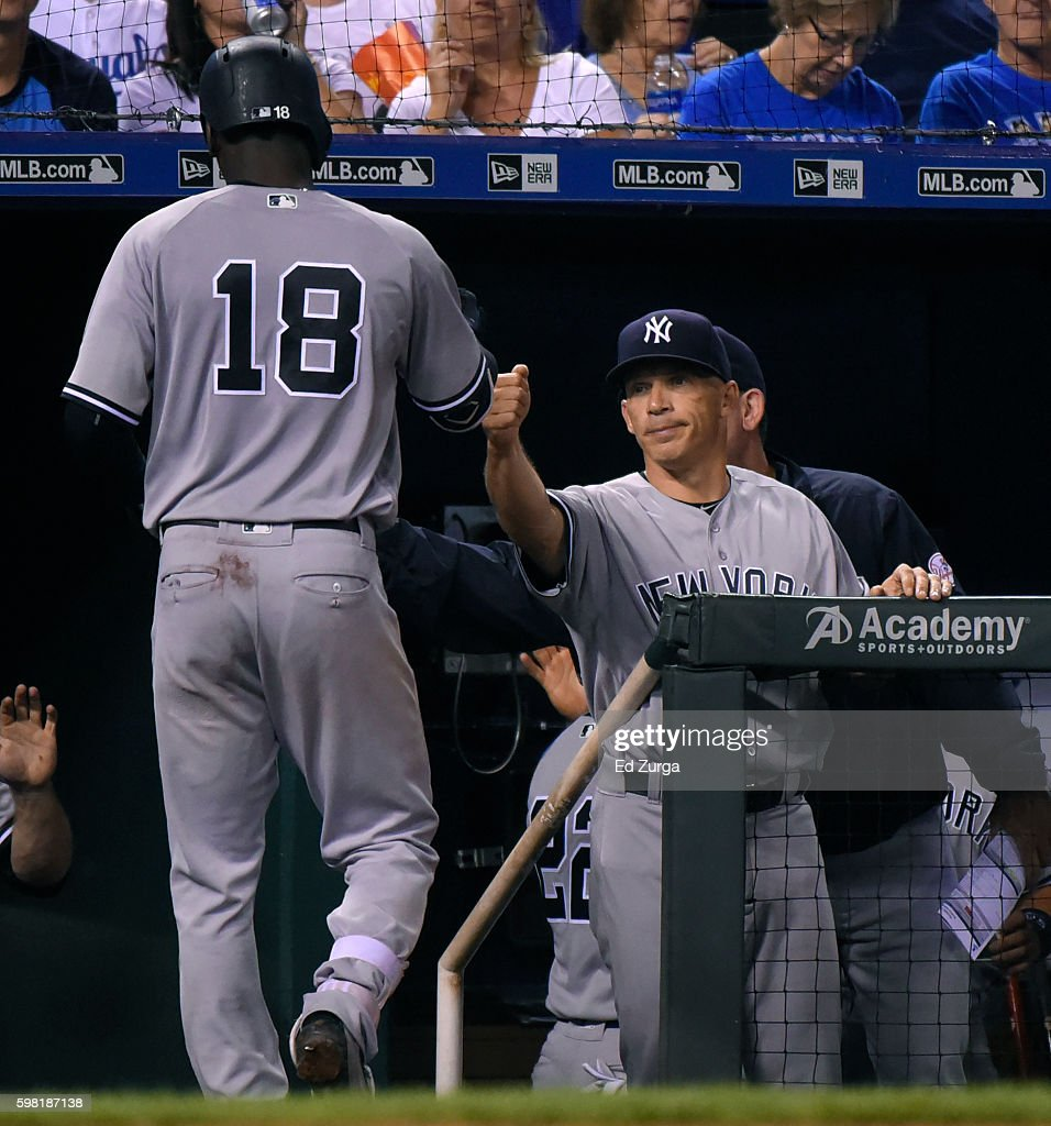 Didi Gregorius #18 of the New York Yankees is congratulated by manager Joe Girardi #28 after hitting a sacrifice fly in the sixth inning against the Kansas City Royals at Kauffman Stadium on August 31, 2016 in Kansas City, Missouri.
