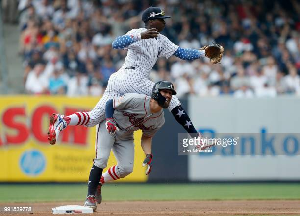 Didi Gregorius of the New York Yankees leaps over Ender Inciarte of the Atlanta Braves after a force out at second base during the first inning at...