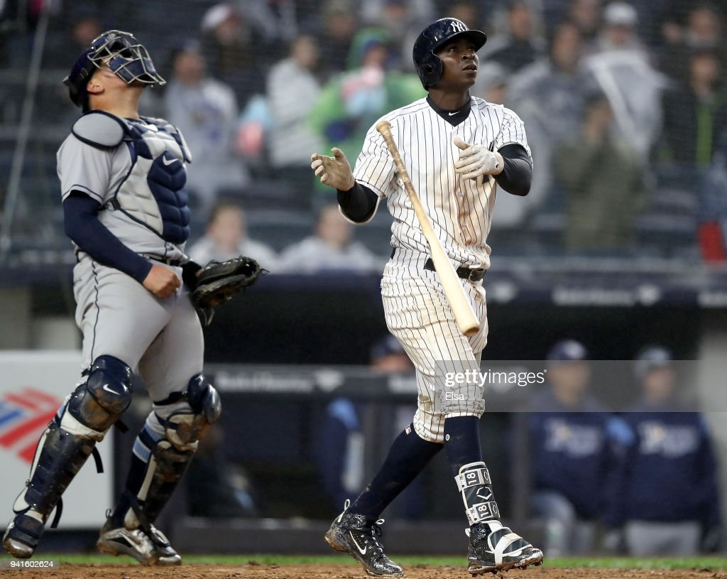 Didi Gregorius #18 of the New York Yankees reacts after he hit a three run home run in the seventh inning as Jesus Sucre #45 of the Tampa Bay Rays reacts during Opening Day at Yankee Stadium on April 3, 2018 in the Bronx borough of New York City.