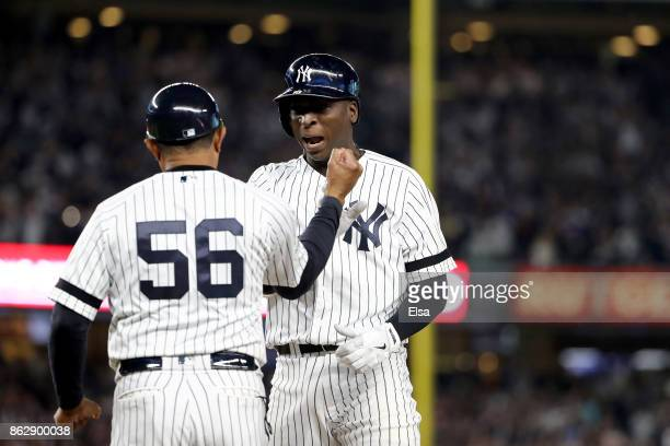 Didi Gregorius of the New York Yankees reacts with first base coach Tony Pena after hitting a single scoring Aaron Judge during the fifth inning...