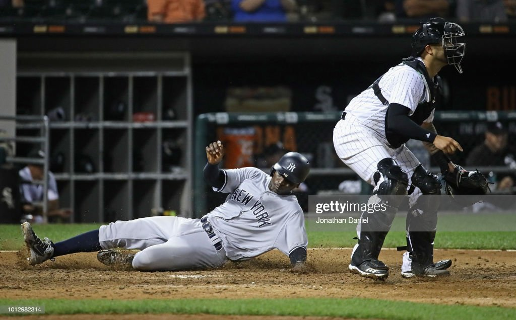 Didi Gregorius #18 of the New York Yankees slides in to score the game winning run in the 13th inning as Omar Narvaez #38 of the Chicago White Sox awaits the late throw at Guaranteed Rate Field on August 7, 2018 in Chicago, Illinois. The Yankees defeated the White Sox 4-3 in 13 innings.