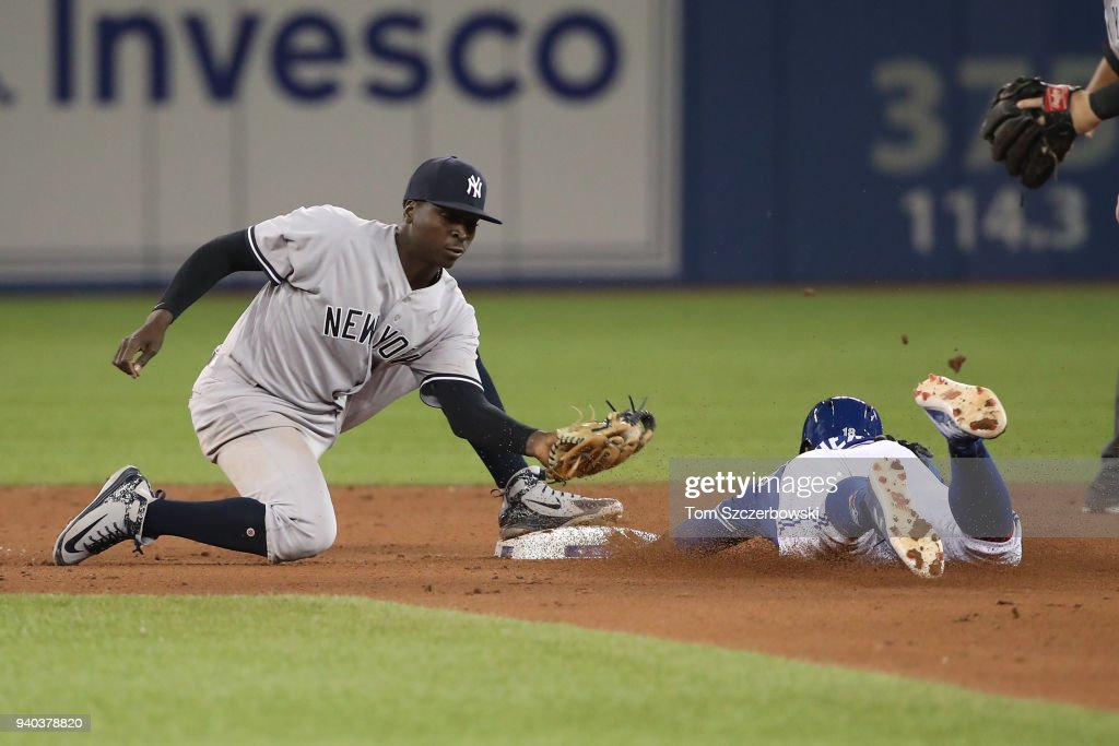 Didi Gregorius #18 of the New York Yankees tags out Curtis Granderson #18 of the Toronto Blue Jays in the seventh inning during MLB game action at Rogers Centre on March 31, 2018 in Toronto, Canada.