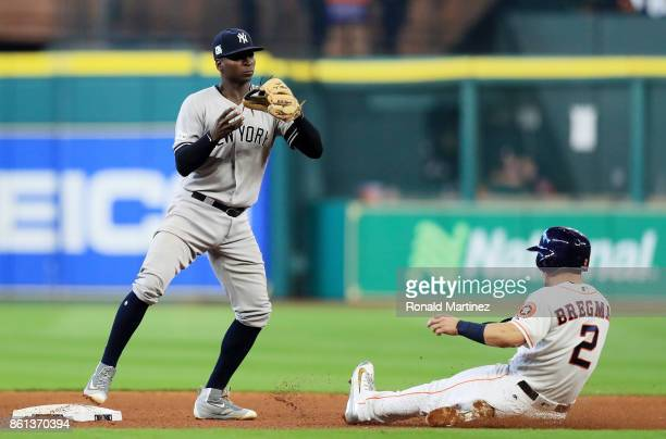 Didi Gregorius of the New York Yankees turns a double play for outs on Alex Bregman and Brian McCann of the Houston Astros in the fifth inning during...