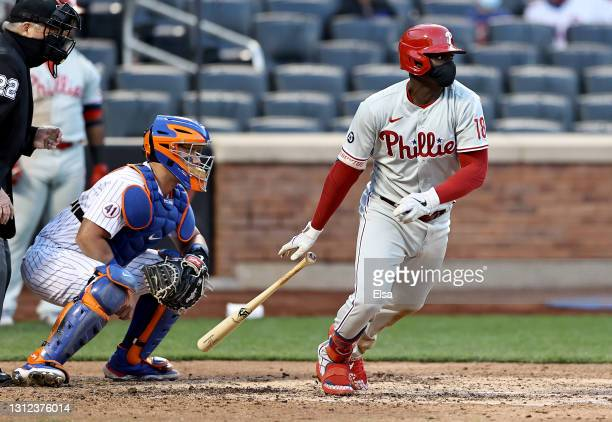 Didi Gregorius of the Philadelphia Phillies drives in a run as James McCann of the New York Mets defends in the eighth inning during game one of a...