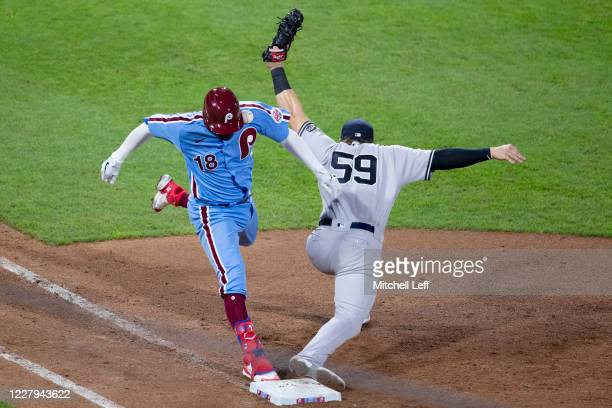 Didi Gregorius of the Philadelphia Phillies is hit with the throw to Luke Voit of the New York Yankees for an infield single in the bottom of the...