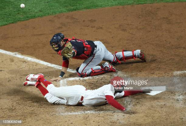 Didi Gregorius of the Philadelphia Phillies slides safely into home plate as Yan Gomes of the Washington Nationals cant handle the throw in the sixth...