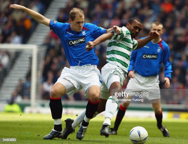 Didier Agathe of Celtic is tackled by Robert Malcolm of Rangers during the Bank Of Scotland Scottish Premier League match between Rangers and Celtic...