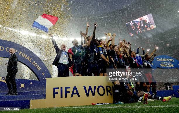 Didier Deschamps Manager of France celebrates by waving a French flag as Hugo Lloris of France lifts the World Cup trophy following the 2018 FIFA...