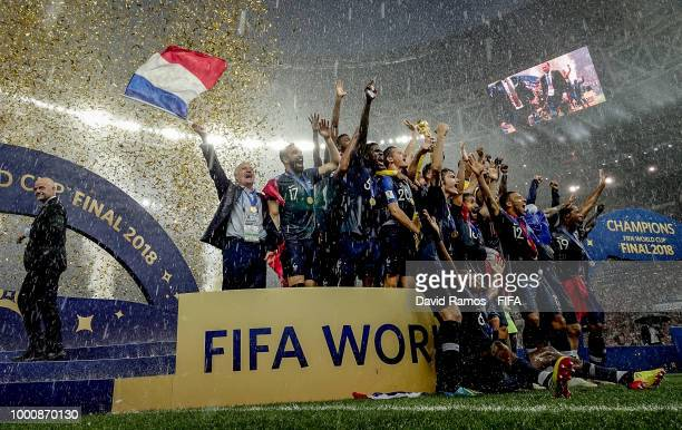 Didier Deschamps Manager of France celebrates waving a French flag as Hugo Lloris of France lifts the trophy following the 2018 FIFA World Cup Russia...