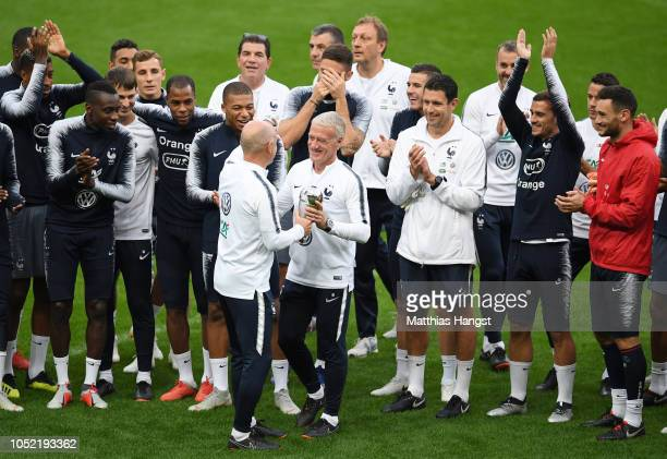Didier Deschamps Manager of France is seen holding The FIFA Best Men's Coach Award surrounded by his team during a France training session at Stade...