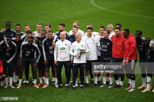 Didier Deschamps, Manager of France is seen holding The FIFA Best Men's Coach Award surrounded by his team during a France training session at Stade...