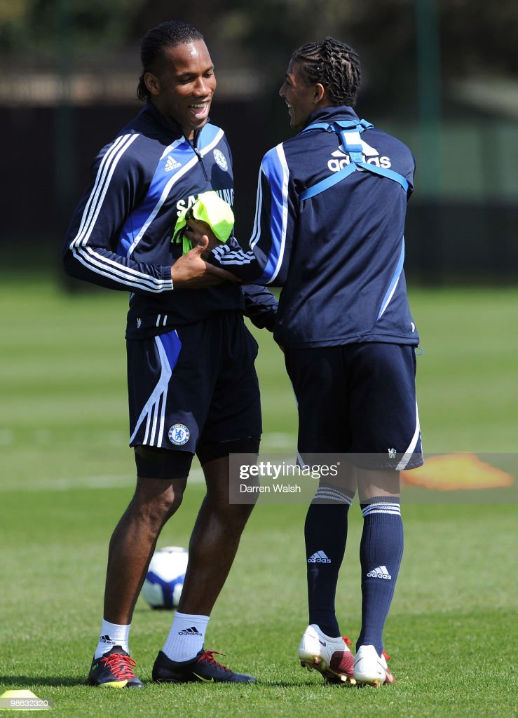 Didier Drogba and Patrick Van Aanholt of Chelsea share a joke during a training session at the Cobham Training Ground on April 23, 2010 in Cobham, England.