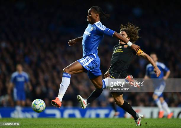 Didier Drogba of Chelsea breaks clear of Carles Puyol of Barcelona during the UEFA Champions League Semi Final first leg match between Chelsea and...