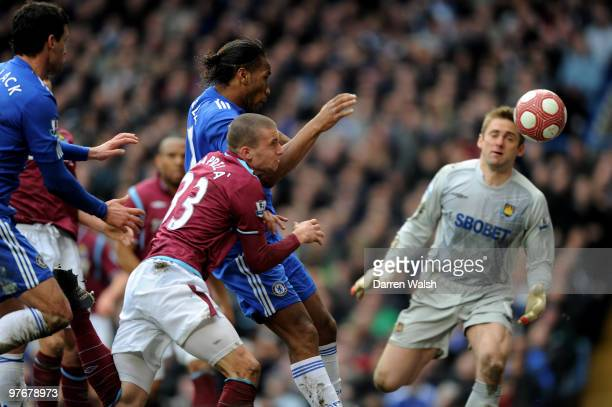 Didier Drogba of Chelsea holds off Fabio Daprela of West Ham to score his team's second goal during the Barclays Premier League match between Chelsea...