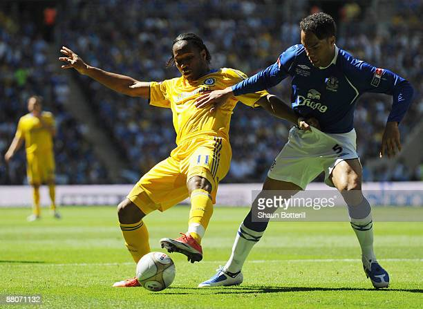Didier Drogba of Chelsea is challenged by Joleon Lescott of Everton during the FA Cup sponsored by EON Final match between Chelsea and Everton at...