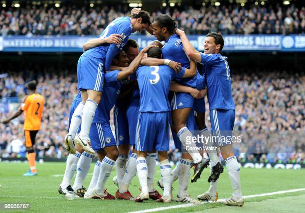 Didier Drogba of Chelsea is congratulated by teammates after scoring his team's fifth of the match and his club's 100th of the season during the...