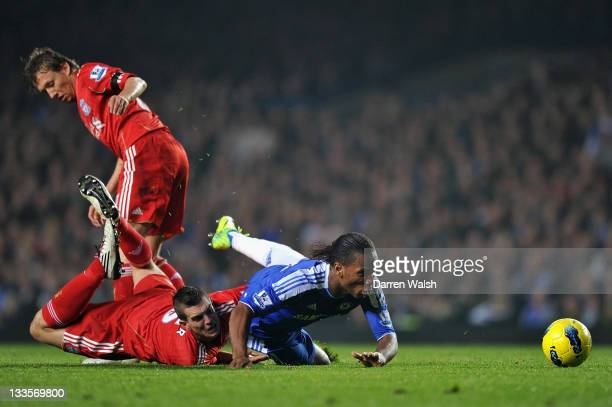 Didier Drogba of Chelsea is tackled by Daniel Agger of Liverpool during the Barclays Premier League match between Chelsea and Liverpool at Stamford...