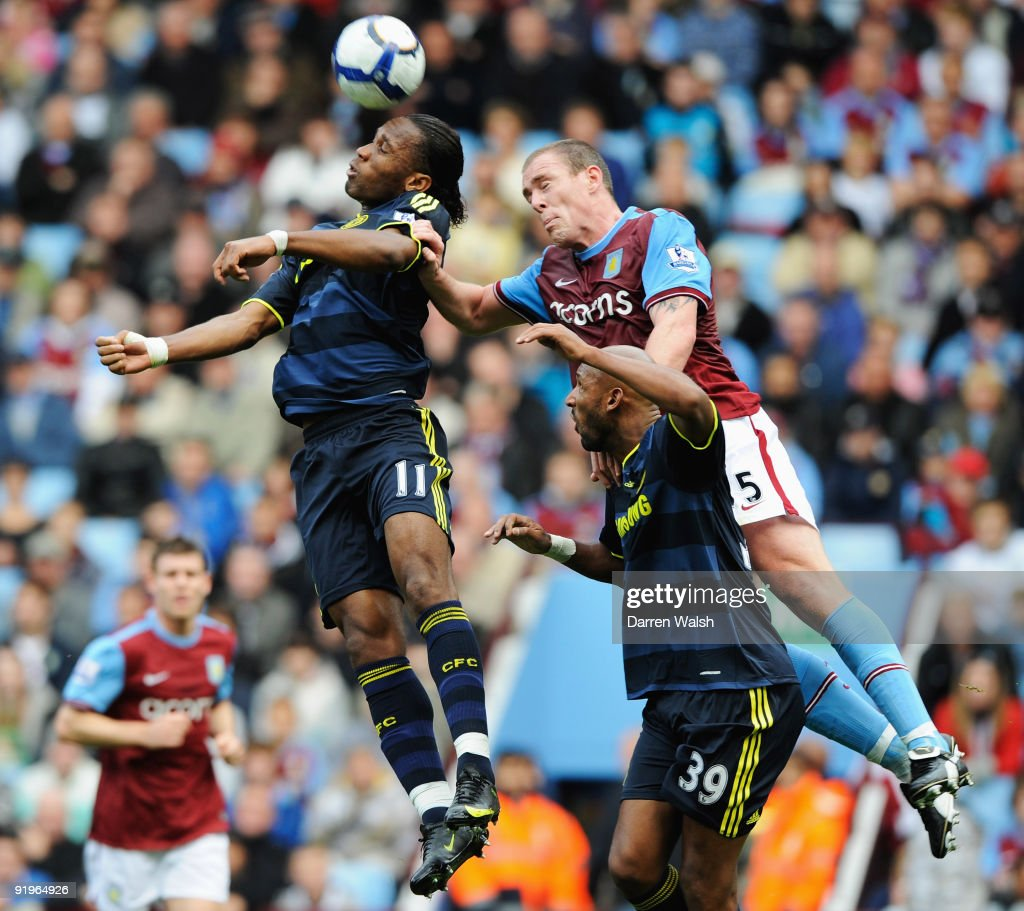 Didier Drogba of Chelsea (L) jumps with Richard Dunne of Aston Villa (R) during the Barclays Premier League match between Aston Villa and Chelsea at Villa Park on October 17, 2009 in Birmingham, England.