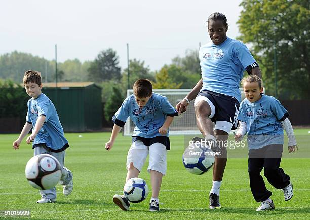 Didier Drogba of Chelsea plays football with some children during the launch of Chelsea FC's partnership with Capital Radio's charity Help a London...