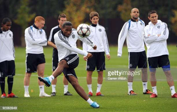 Didier Drogba of Chelsea practices taking freekicks as his team mates look on during a training session at the Cobham training ground on October 20...