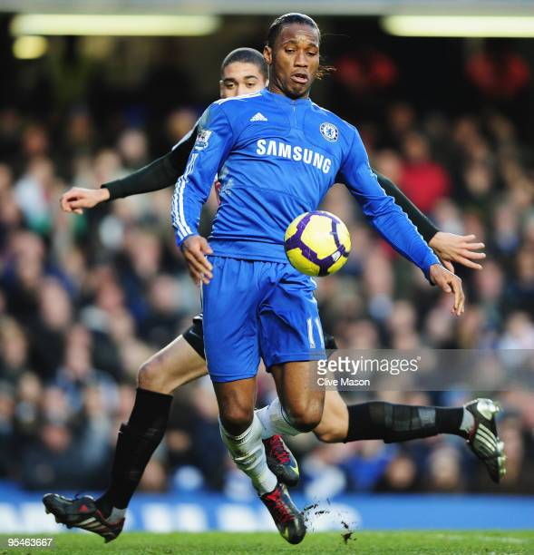 Didier Drogba of Chelsea shields the ball from Chris Smalling of Fulham during the Barclays Premier League match between Chelsea and Fulham at...