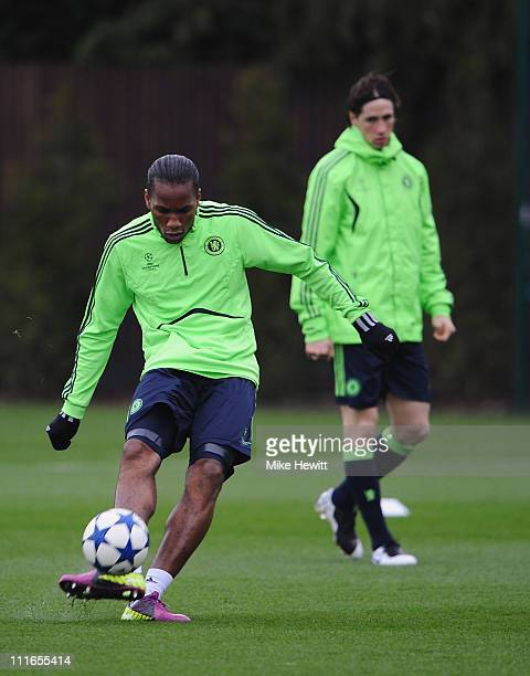 Didier Drogba of Chelsea shoots as team mate Fernando Torres looks on during a Chelsea training session ahead of their UEFA Champions League...