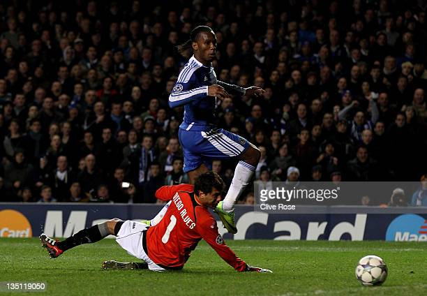 Didier Drogba of Chelsea slips the ball past goalkeeper Diego Alves of Valencia to score his team's third goal during the UEFA Champions League group...