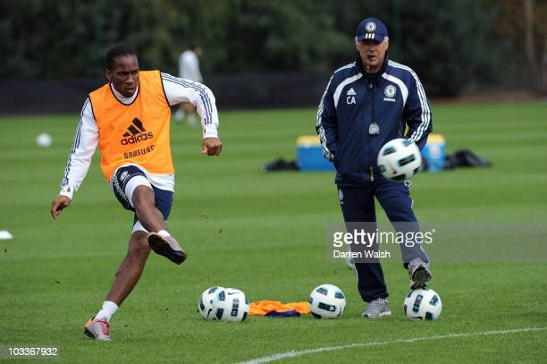 Didier Drogba of Chelsea watched by Carlo Ancelotti during a training session at the Cobham training ground on August 13, 2010 in Cobham, England.