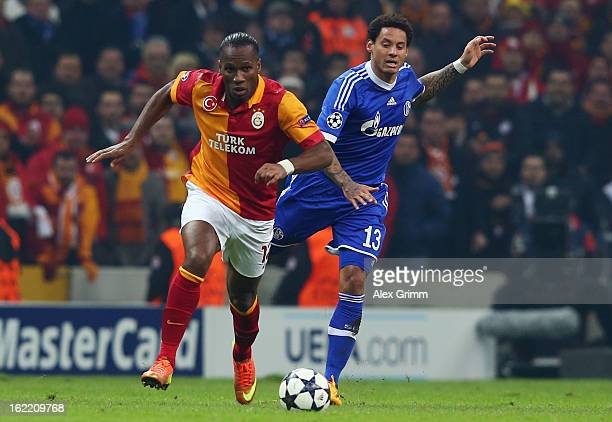Didier Drogba of Galatasaray is challenged by Jermaine Jones of Schalke during the UEFA Champions League Round of 16 first leg match between...