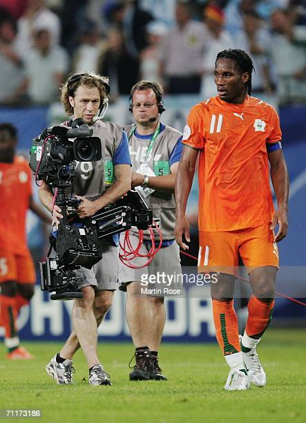 Didier Drogba of Ivory Coast walks dejectedly from the pitch pursued by a TV Cameraman at the the end of the FIFA World Cup Germany 2006 Group C...