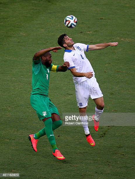 Didier Drogba of the Ivory Coast and Konstantinos Manolas of Greece go up for a header during the 2014 FIFA World Cup Brazil Group C match between...