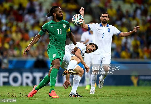 Didier Drogba of the Ivory Coast and Sokratis Papastathopoulos of Greece compete for the ball during the 2014 FIFA World Cup Brazil Group C match...