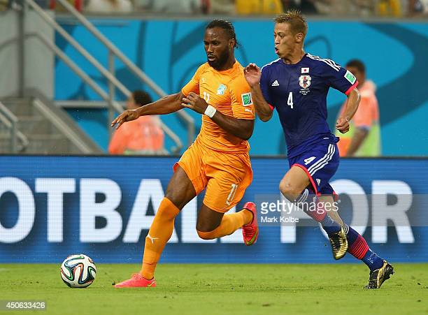Didier Drogba of the Ivory Coast controls the ball against Keisuke Honda of Japan during the 2014 FIFA World Cup Brazil Group C match between the...