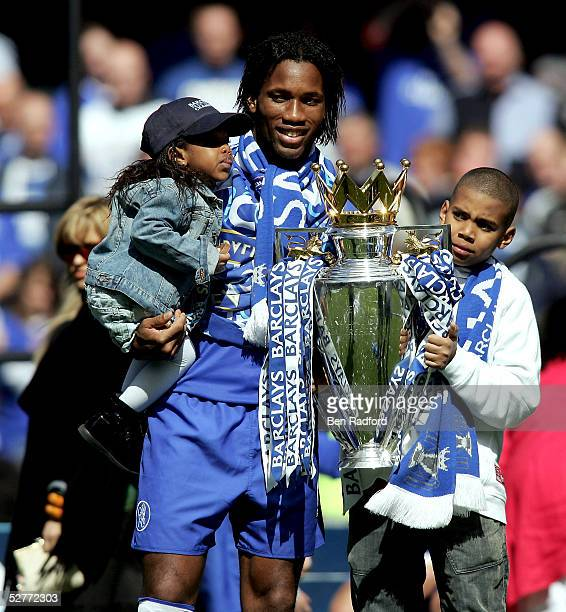 Didier Drogba poses with his children and the Barclays Premiership Trophy at Stamford Bridge on May 7 2005 in London England