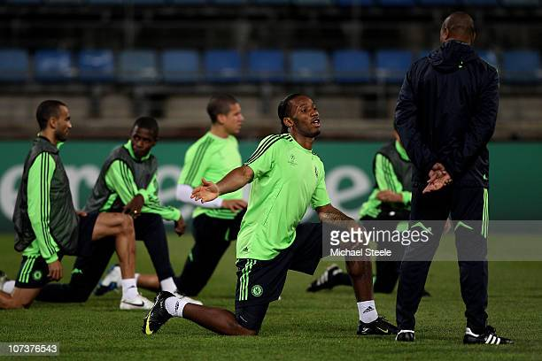 Didier Drogba speaks with assistant coach Michael Emenalo during the Chelsea training session ahead of their UEFA Champions League Group F match...
